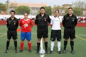 El trio arbitral con las capitanas del partido