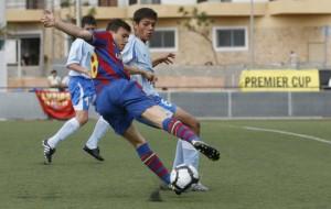 Un futbolista del Barça trata de recortar a otro del Portmany en el partido disputado ayer por la mañana  Vicent Marí