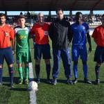 El trío arbitral con los capitanes y el cuarto árbitro